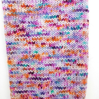 Crocus Fleur hand dyed yarn by Fiber Lily Australia purple, citrus, pink and turquoise speckles knit sample